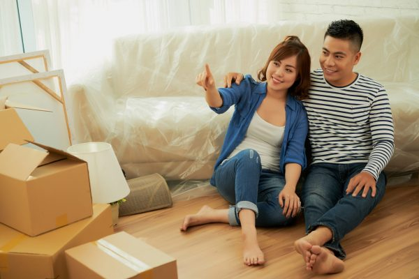 Smiling Asian couple discussing how they will design new apartment