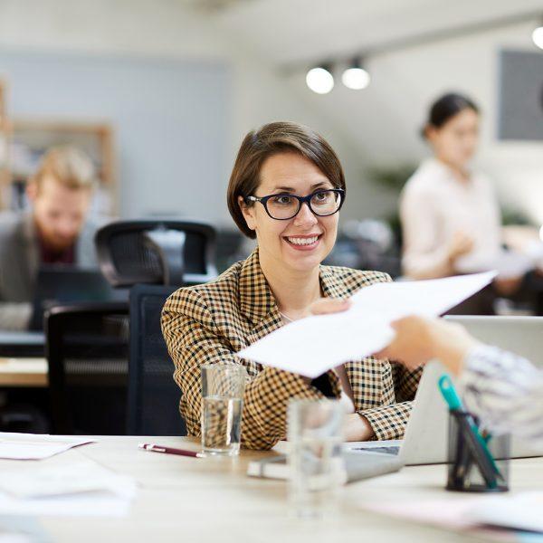 smiling-businesswoman-giving-documents-to-YLNUKBJ.jpg