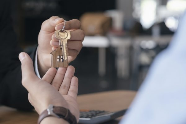 Close up view of young man taking keys from real estate agent during meeting after signing rental lease contract or sale purchase agreement. Young man purchasing new home. Real estate buy or rent or home insurance concept.